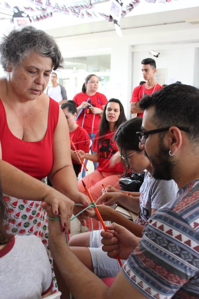 Oficineira da oficina de maxi tricô orientando os alunos